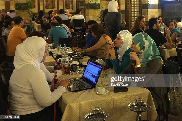 Modern veiled women sit in a restaurant surfing the net and smoking cigarette and a waterpipe in a popular restaurant in Bab Tuma neighborhood on May...