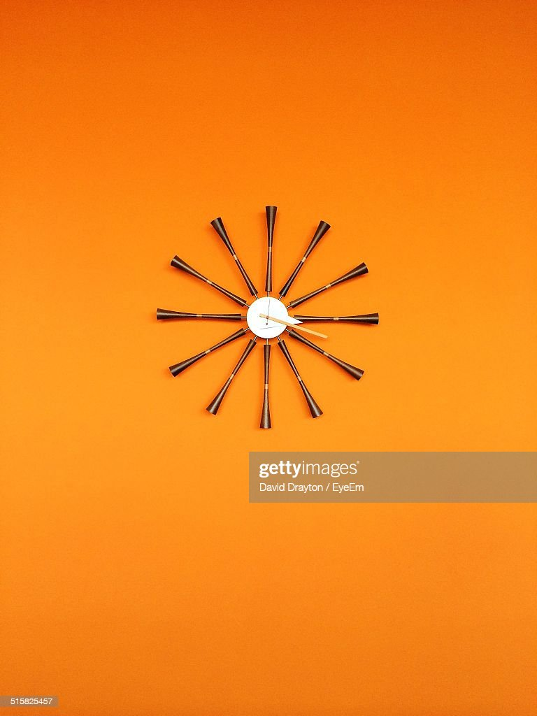 Modern Wall Clock On Orange At Home Stock Photo