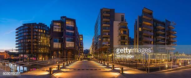 Modern waterfront apartments illuminated at dusk Aker Brygge Oslo Norway