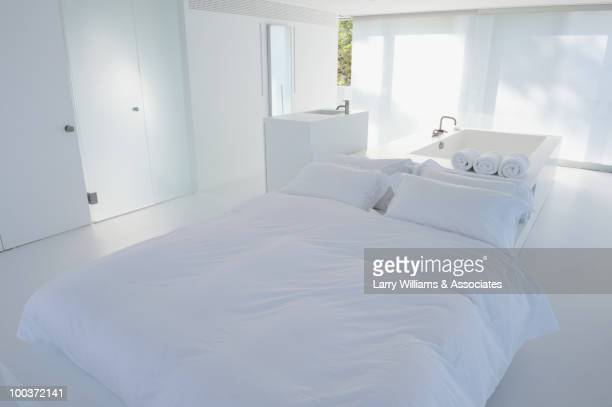 Modern, white bedroom with tub in background