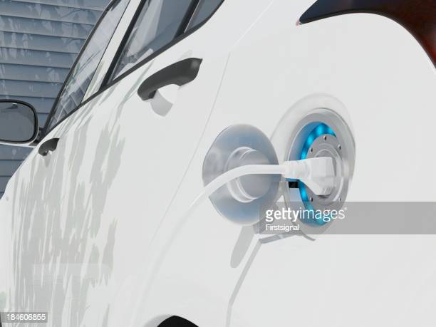 A modern, white electric car recharging