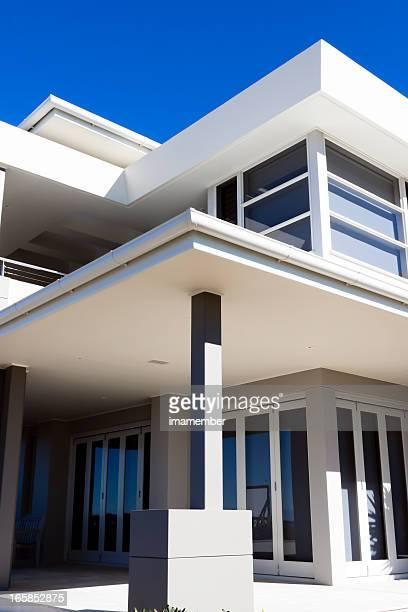 Modern white house in sunlight against blue sky, copy space