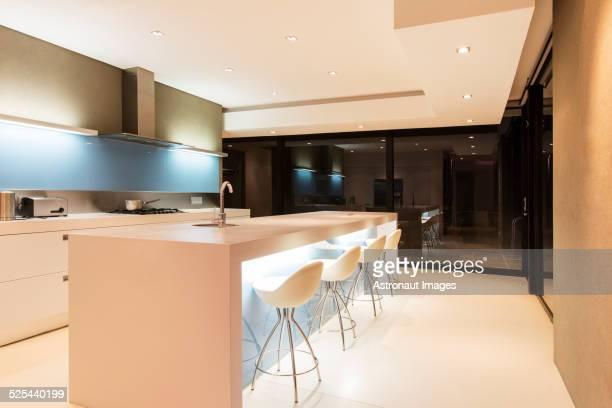 Modern white kitchen with kitchen island and stools illuminated at night