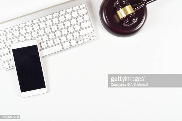 Modern white legal office desk table with smartphone, judges gravel and computer keyboard top view, flat lay