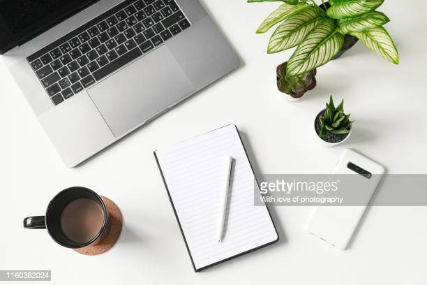 modern white office desk table with laptop, smartphone and blank notebook and cup of coffee, flatlay, top view workspace, business - bureau stockfoto's en -beelden