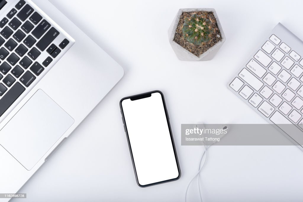 Modern white office work table with smartphone mock up laptop ,earphone and cactus, top view : Stock Photo