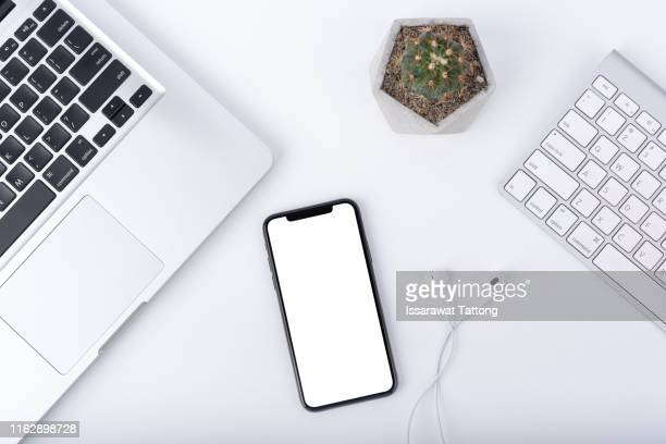 modern white office work table with smartphone mock up laptop ,earphone and cactus, top view - iphone mockup stock pictures, royalty-free photos & images