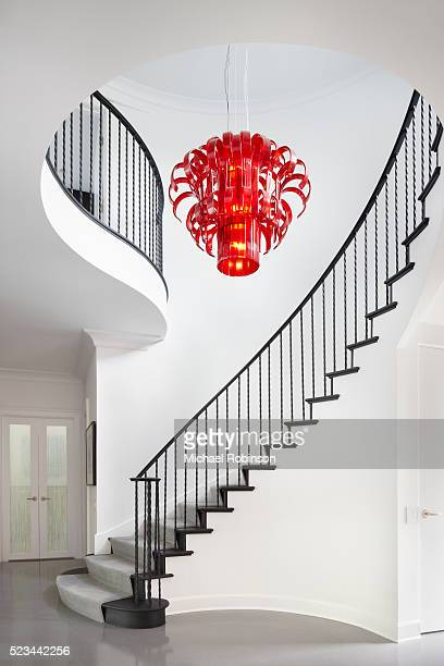 modern winding staircase with red chandelier, chicago il - michael robinson stock pictures, royalty-free photos & images