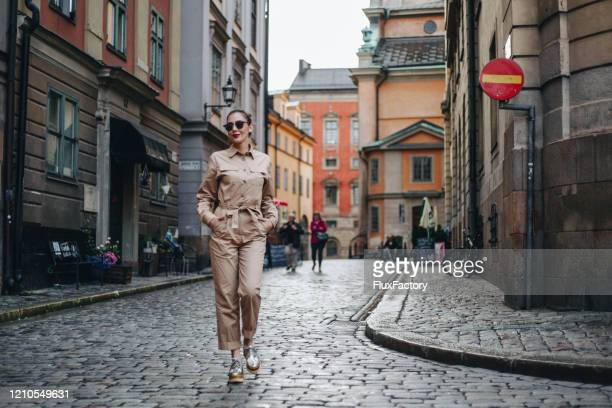 modern woman exploring rainy stockholm - jumpsuit stock pictures, royalty-free photos & images