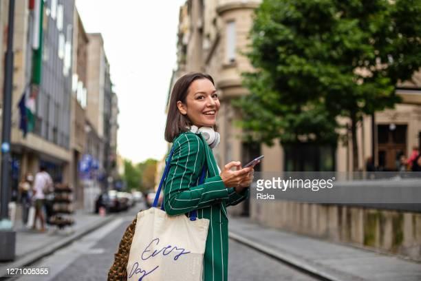 路上で現代の女性、仕事から戻ってくる - street style ストックフォトと画像