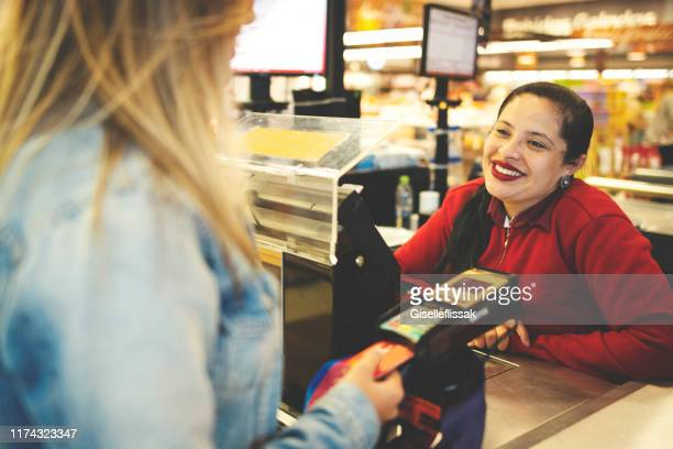 modern woman paying purchases at supermarket checout using credit card - convenience store stock pictures, royalty-free photos & images