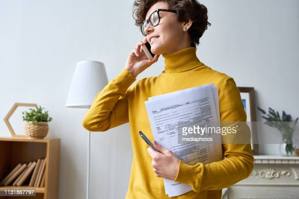 modern woman with tax papers talking on phone - filing documents stock pictures, royalty-free photos & images