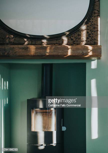 modern wood burning stove surrounded by a green wall below a large mirror - warming up stock pictures, royalty-free photos & images