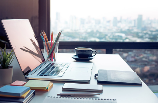 Modern work table with computer laptop and cityscapes view from window.Business concepts ideas 1093508248