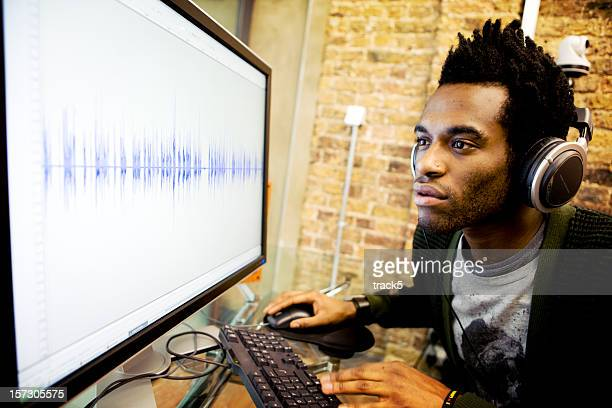 modern workplace: audio engineer editing a waveform on his computer