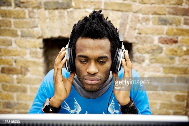 modern workplace: creative professional listening to music through his headphones
