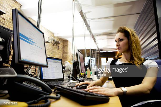 modern workplace: female professional computer programmer working at her desk