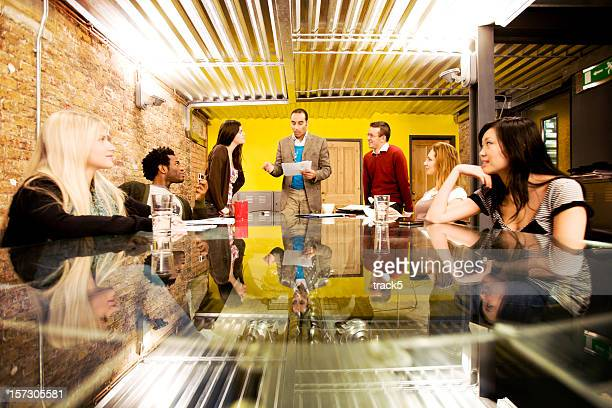 modern workplace: meeting of creative professionals listening to their manager - pep talk stock pictures, royalty-free photos & images