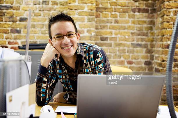 modern workplace: relaxed office professional sitting smiling at his desk