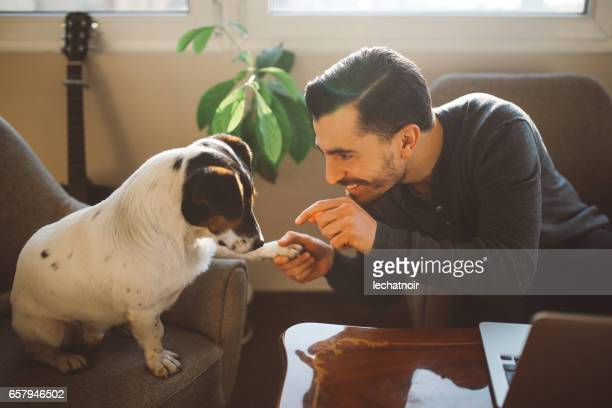 Modern young man at home playing with pet dog