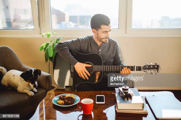 Modern young man practicing guitar at home