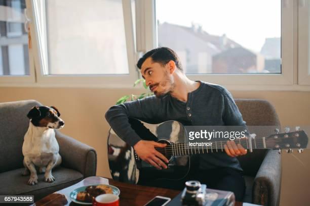 現代の若い男が家でギターを練習