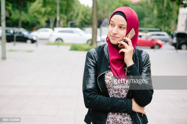 moderne jonge moslimvrouw draagt hijab gebruik mobiele telefoon