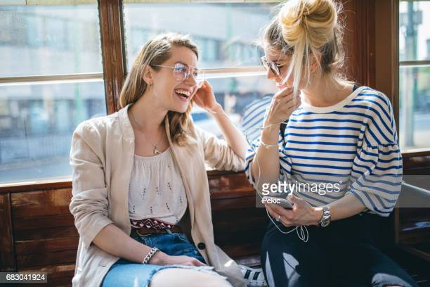 Modern young women listening to music in city transportation
