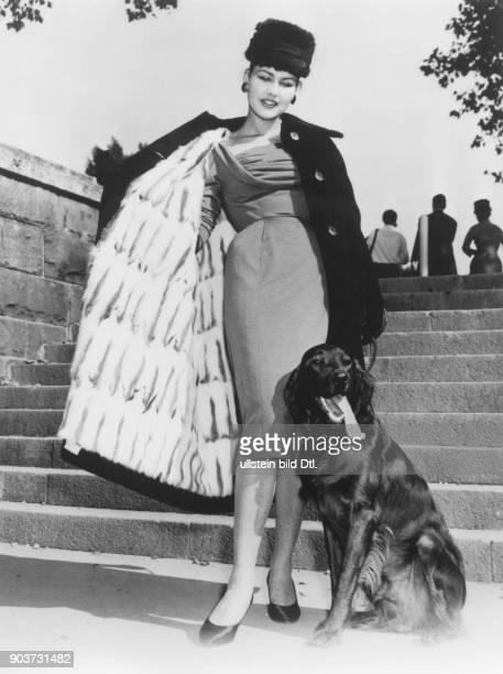 * Modeschöpfer D Modell 'Baku' Kleid aus grünem Wolljersey mit einem schwarzen Cape mit Pelzfutter September 1956