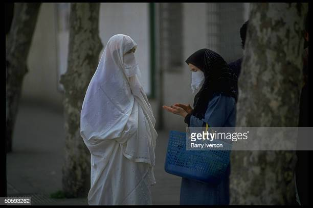 Modestly veiled Islamic women poised chatting on street re rise of fundamentalist power FIS elections victorysparked milbacked coup