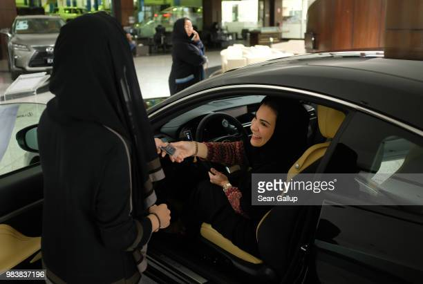 Modia Batterjee receives the keys to a Lexus car she is interested in buying from saleswoman Haifa Alsehli at a Lexus dealership the day after women...
