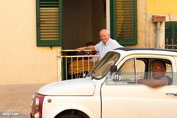 Modica, Sicily: Man Drives Vintage Fiat 500 Past Open Window