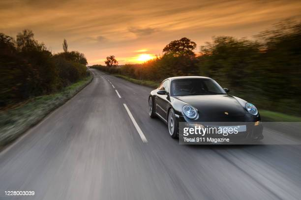 Modified Porsche 997 Carrera S sports car driving on a rural road with a sunset visible in the background, taken on November 20, 2019.