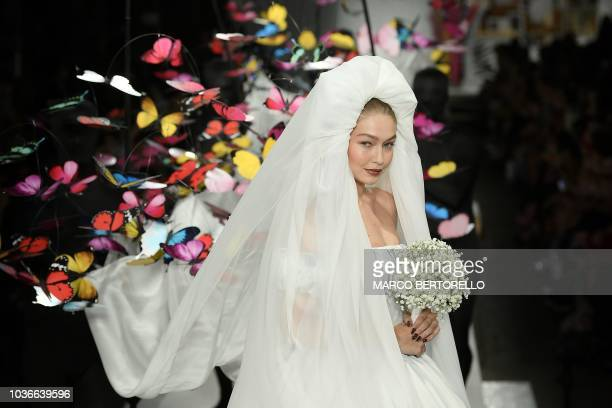 Modl Gigi Hadid presents a creation for Moschino fashion house during the Women's Spring/Summer 2019 fashion shows in Milan on September 20 2018