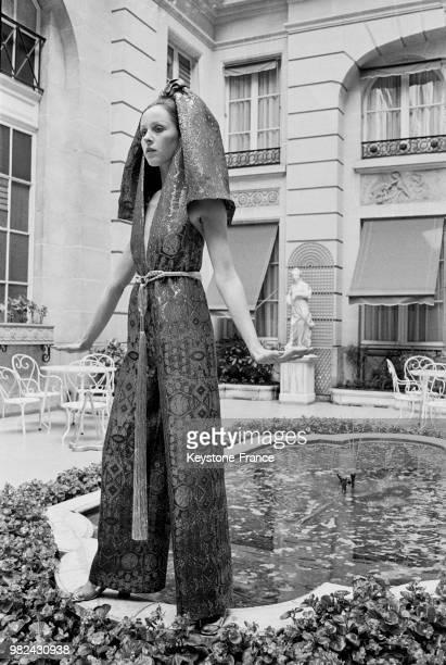 Modèle portant une robe du soir et un pantalon en lame lors du défilé de Jacques Esterel à l'hôtel de Crillon à Paris en 1969 France