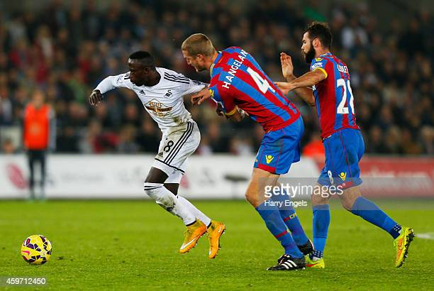 Modou Barrow of Swansea City evades Brede Hangeland and Joe Ledley of Crystal Palace during the Barclays Premier League match between Swansea City...
