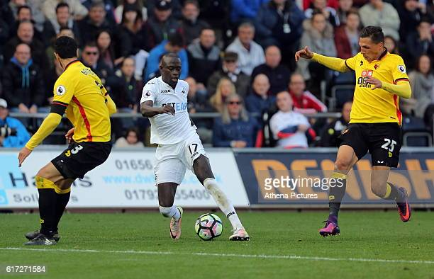 Modou Barrow of Swansea City gets past Miguel Britos and Jose Holebas of Watford during the Premier League match between Swansea City and Watford at...