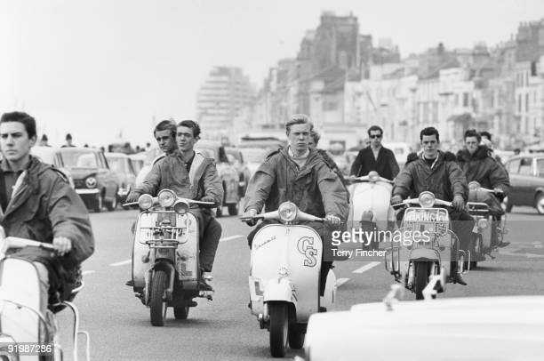 Mods ride their scooters along the seafront at Hastings, East Sussex, 4th August 1964.