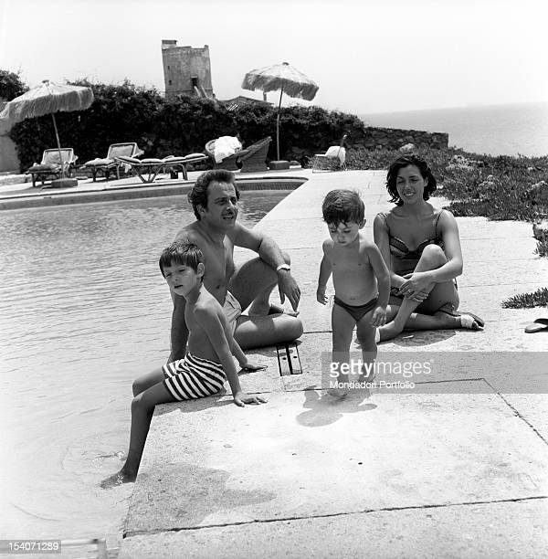 Modugno family portrait in swimming costume from left the eldest son Marco the singersongwriter Domenico the youngest son Marcello and the actress...