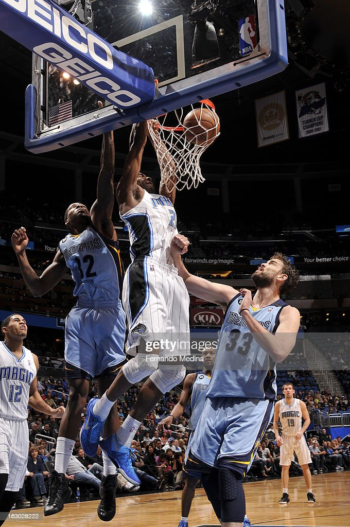 Moe Harkless #21 of the Orlando Magic dunks against Ed Davis #32 and Marc Gasol #33 of the Memphis Grizzlies on March 3, 2013 at Amway Center in Orlando, Florida.