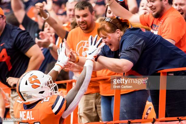 Moe Neal of the Syracuse Orange celebrates his touchdown carry with fans during the first quarter against the Western Michigan Broncos at the Carrier...