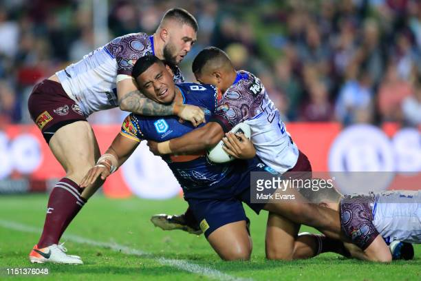 Moeaki Fotuaika of the Titans ios tackled during the round 11 NRL match between the Manly Sea Eagles and the Gold Coast Titans at Lottoland on May...