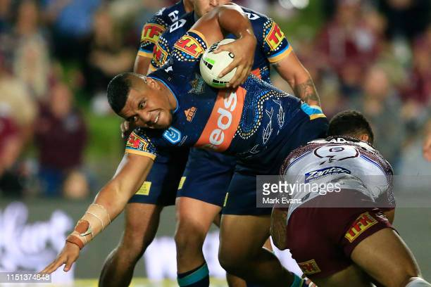 Moeaki Fotuaika of the Titans is tackled during the round 11 NRL match between the Manly Sea Eagles and the Gold Coast Titans at Lottoland on May 24,...