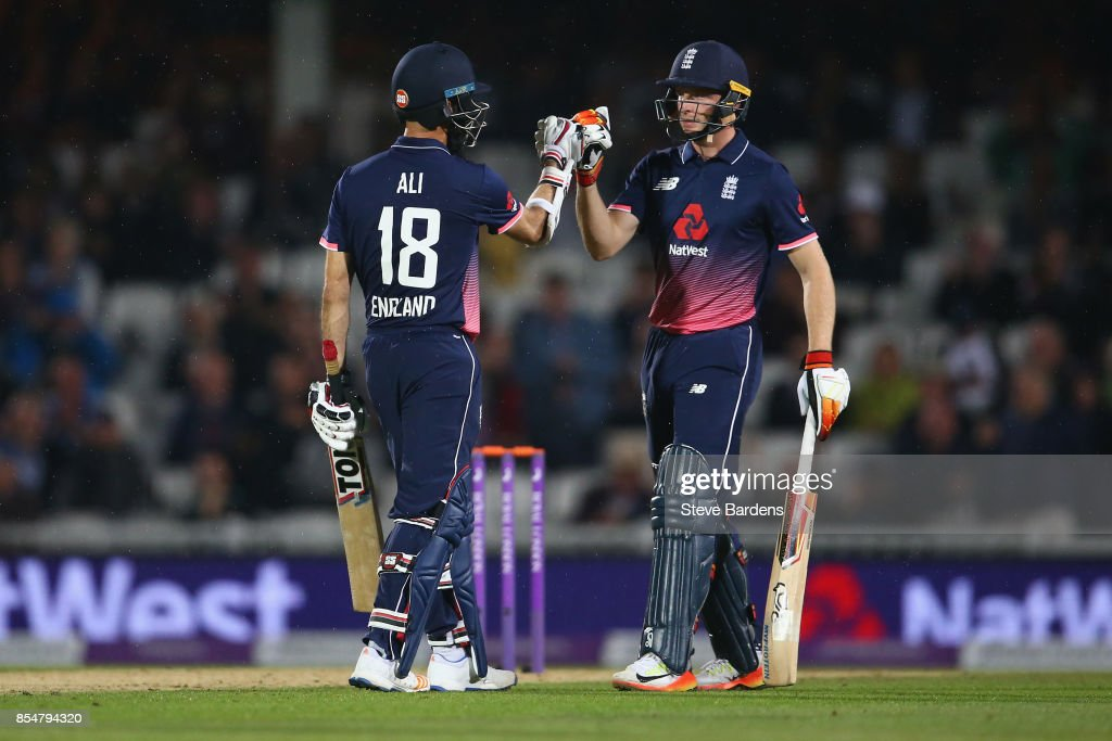Moeen Ali (L) and Jos Buttler of England fist bump as rain stops play during the 4th Royal London One Day International between England and West Indies at The Kia Oval on September 27, 2017 in London, England.