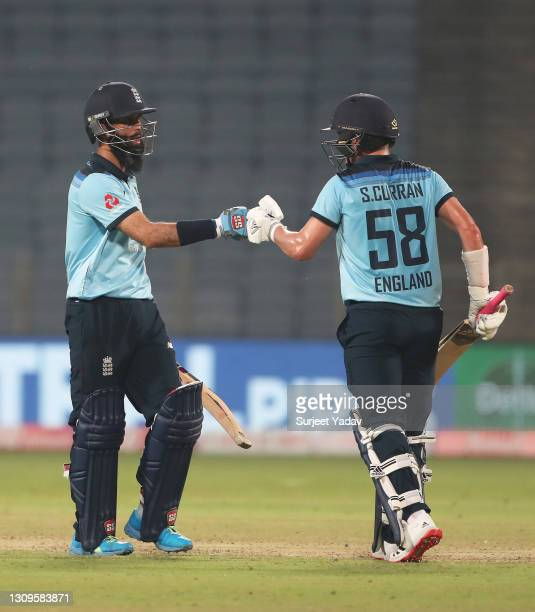 Moeen Ali and Sam Curran of England interact during the 3rd One Day International match between India and England at MCA Stadium on March 28, 2021 in...
