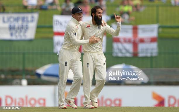 Moeen Ali celebrates with Jos Buttler of England after the dismissal of Niroshan Dickwella during the 2nd Cricket Test Match between Sri Lanka and...