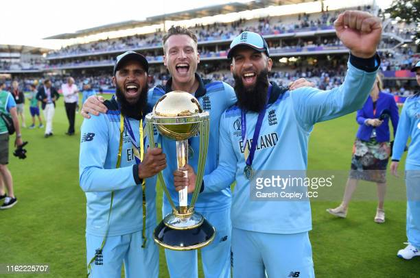 Moeen Ali, Jos Buttler and Adil Rashid celebrate with the trophy after winning the Final of the ICC Cricket World Cup 2019 between New Zealand and...
