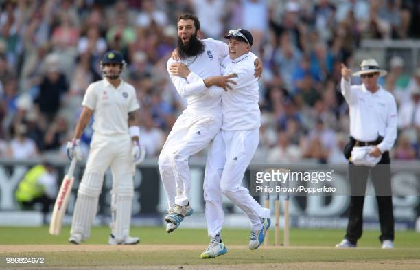 Moeen Ali of England celebrates with teammate Joe Root after dismissing India's Cheteshwar Pujara during the 4th Test match between England and India...