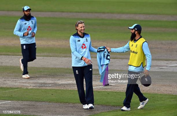 Moeen Ali of England hands Joe Root of England his jumper during the 3rd Royal London One Day International Series match between England and...