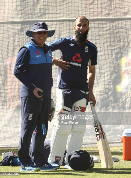 Moeen Ali of England holds his side as he speaks to England Head Coach Trevor Bayliss during an England Ashes series nets session at Adelaide Oval on...